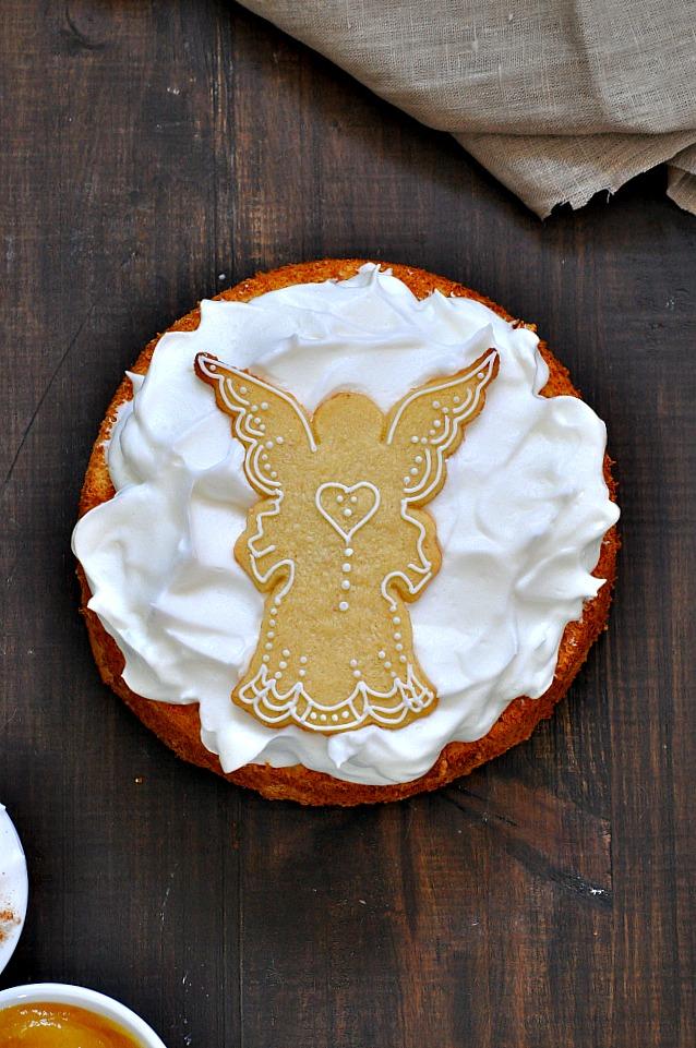Foto cenital de un Angel Food Cake con merengue y una galleta decorada con forma de ángel.