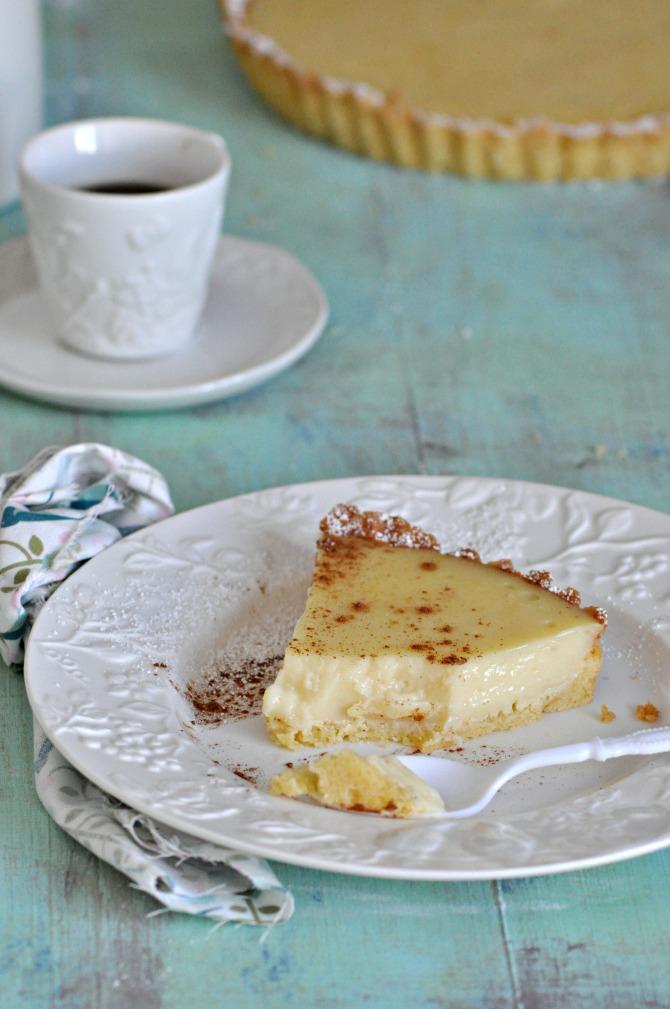Receta de tarta de leche. Porción de tarta espolvoreada con canela y acompañada con un café