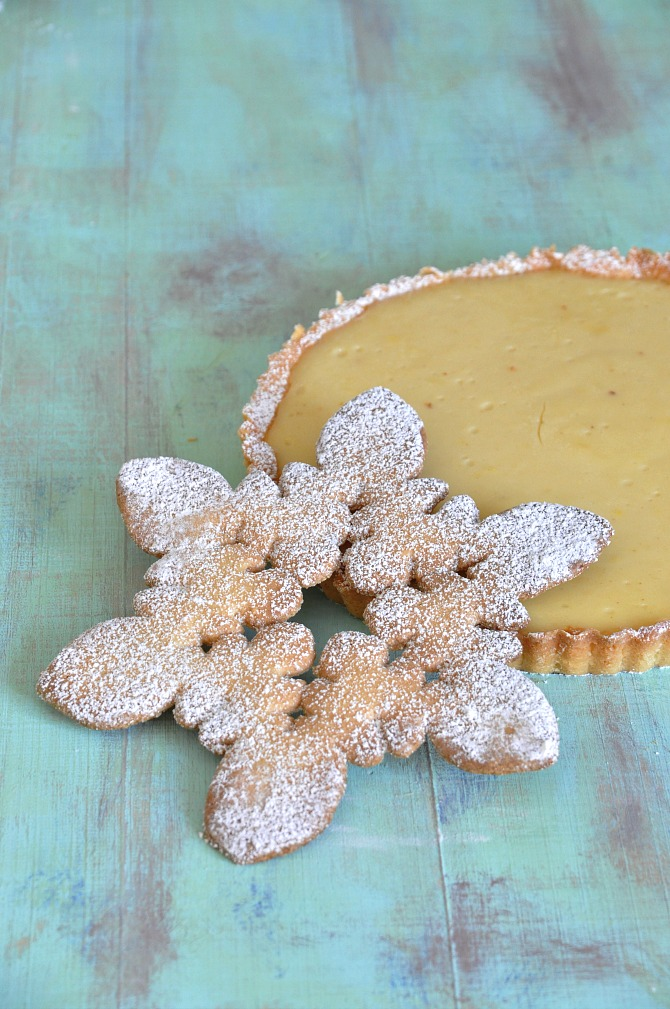 Tarta de leche acompañada con una galleta navideña y espolvoreada con azucar glas
